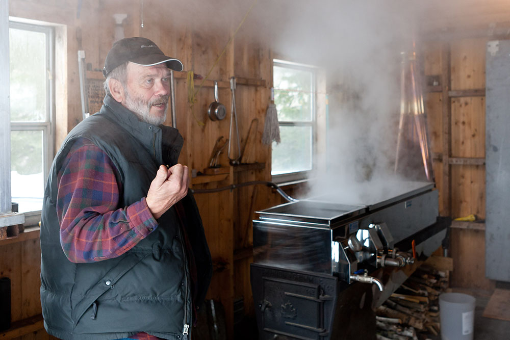 Dennis explains the operation while, behind him, the evaporator boils fresh sap into syrup
